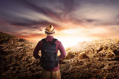 Back view of asian hikers man with hat standing on rocky mountai Stock Photos