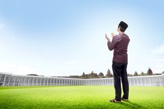 Back view of asian man standing on grass raise the hands and gazing the sky. On the outside the mosque stock photos