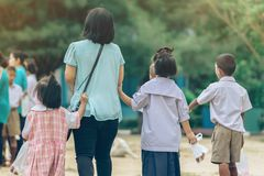 Back view of Asian mother leads her daughter and son to school. royalty free stock image