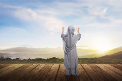 Back view of asian muslim girl with hijab praying stock photo
