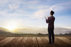 Back view of asian muslim man praying to god. With landscape view background Stock Photos