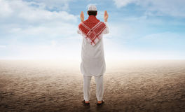 Back view of asian muslim man raising hand and praying stock images