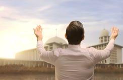 Back view of asian muslim man raising hand and praying Stock Image