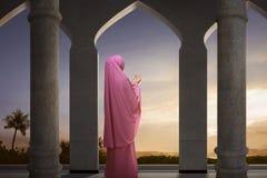 Back view of asian muslim muslim woman raising hand and praying stock photo
