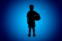 Back view of asian soccer player with football. Studio shot. Silhouette of young asian soccer player holding his soccer ball on blue background, studio shot Royalty Free Stock Photos