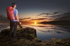 Back view of asian tourist man with camera and backpack looking. At sunset view from the top Royalty Free Stock Images