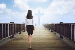 Back view of asian woman walking to cross shape Stock Image