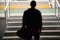 Back view of a athletic man with bag standing at the stadium Royalty Free Stock Image