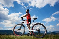 Back view of athletic rider in sportswear and helmet standing with cross country bicycle royalty free stock images