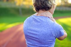 Back view of athletic young woman in sportswear touching her painful neck at the stadium. Sport, health and people concept stock images