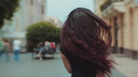 Back view of attractive long-haired curly brunette woman walking down the city-street or alley, turns to camera and. Gives a beautiful smile, wind plays with stock video footage