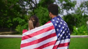 Back view of attractive multiethnic couple embracing each other holding American flag on the back and walking in the. Green field. Patriotic concept stock video footage