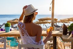 Back view of an attractive woman in a beach bar. Who enjoys the sunset Royalty Free Stock Photo