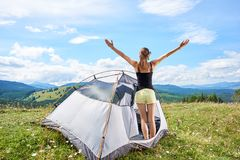 Woman tourist hiking in mountain trail, enjoying summer sunny morning in mountains near tent. Back view of attractive woman hiker hiking mountain trail, standing royalty free stock image