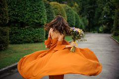 Back view of attractive woman in long orange dress. With bouquet of flowers on the background of road and trees Royalty Free Stock Image