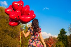 Back view of attractive young woman with red smiling balloons in hand outdoor Stock Photos