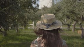 Back view of attractive young woman in straw hat and long white dress running through the green summer garden. Carefree. Rural life, connection with nature stock footage