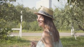 Back view of attractive young woman in straw hat and long white dress running through the green summer garden then. Turning and smiling at the camera. Carefree stock footage