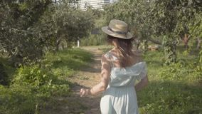 Back view of attractive young woman in straw hat and long white dress running through the green summer garden then. Back view of attractive young woman in a stock video