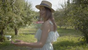 Back view of attractive young woman in straw hat and long white dress walking through the green summer garden then. Back view of attractive young woman in a stock video footage