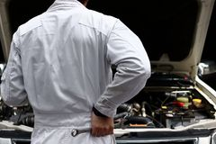 Back view of automotive mechanic in white uniform with wrench diagnosing engine under hood at the repair garage. Car insurance co royalty free stock photo