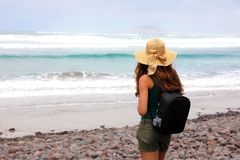 Back view of backpacker female with straw hat looking to La Graciosa Island from Caleta Famara beach, Lanzarote, Spain.  Stock Photography