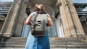 Back view backpacker female tourist approaching entrance medieval building low angle. Steadicam establish shot back view backpacker female tourist approaching stock footage