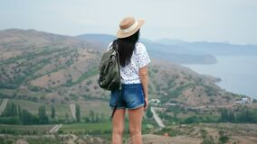 Back view backpacker woman admiring nature with mountains and sea. 4k Dragon RED camera