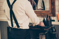 Back view of a barber shop stylist organizing his tools and equipment, he is wearing white shirt and black suspenders stock photos