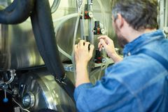 Bearded Brewer Adjusting Pressure. Back view of bearded brewer wearing denim shirt adjusting pressure in cylindrical beer maturation tank while working at modern Royalty Free Stock Image