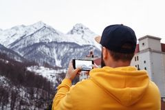 Back view. Bearded male tourist in yellow hoodie and cap stands on background of high snowy mountains, makes photos on smartphone stock photography