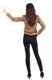 Back view of of beautiful brunette woman in brown jacket  makes Stock Photo