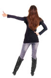 Back view of of beautiful brunette woman in jeans going thumb up Royalty Free Stock Image