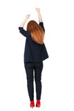 Back view of Beautiful business woman in suite looking at wall and Holds  hand up. Stock Photography