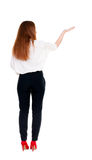 Back view of Beautiful business woman in suite looking at wall and Holds  hand up. Stock Images