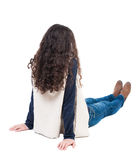 Back view beautiful curly woman sitting on floor and looks into Royalty Free Stock Images