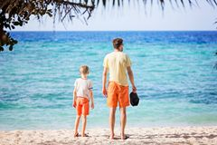 Family on vacation. Back view of beautiful family of two, father and son, standing together at the beach enjoying summer vacation, white sand beach and turquoise Royalty Free Stock Photo