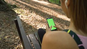 Back view of Beautiful girl with earphones using smartphone with green screen, outdoors in the park. Beautiful fitness girl using mobile phone outdoors, sitting stock footage