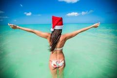 Back view of beautiful girl in santa hat walking Stock Images
