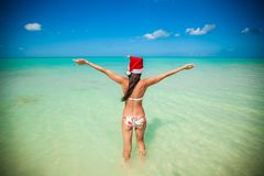 Back view of beautiful girl in santa hat walking Royalty Free Stock Photo