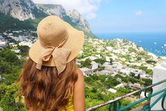 Back view of beautiful girl with straw hat looking at Capri sight from terrace, Capri Island, Italy Stock Photos