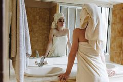 Back view of beautiful girl in towels looking at mirror. In bathroom royalty free stock photo