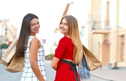 Back view of two beautiful girls with shopping bags stock photography