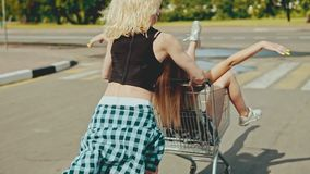 Back view of beautiful hipster teen girls riding in shopping cart at parking stock footage