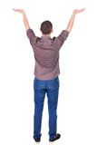 Back view of Beautiful man in jeans looking at wall and Holds  h. And up.  young brunette standing. Rear view people. Isolated over white background. Man in a Stock Photography