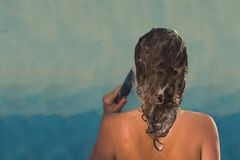 Back view of beautiful naked young woman taking shower in shower cabin. royalty free stock photo
