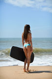 Back view of beautiful young woman holding surfboard in her hand on a beach at sunset or sunrise background Stock Image