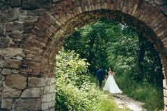 Back view of the beautiful walking newlywed couple by the hand along the path of the green forest. Look through the old. Stone arch Stock Images