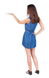 Back view of Beautiful woman in jeans dress and sandals Holds  h. And up. Rear view people collection.  backside view of person.  Isolated over white background Royalty Free Stock Image