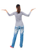 Back view of Beautiful woman in  jeans. Looking at wall and Holds a hand up. Rear view people collection.  backside view of person.  Isolated over white Royalty Free Stock Photography